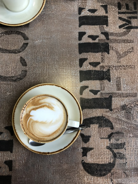 Cup of flat white coffee on coffee bean sack